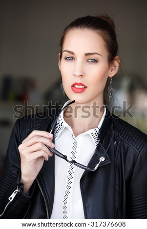 Sexy fashionable caucasian brunette woman in leather jacket holding sunglasses - stock photo