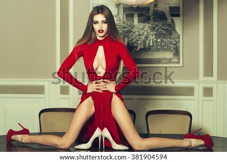 Sexy fashionable glamour young woman with long hair straight body and slim legs in red dress and shoes sitting on table indoor, horizontal picture