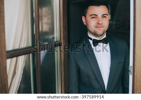 Sexy fashionable man celebrity in tuxedo indoor - stock photo
