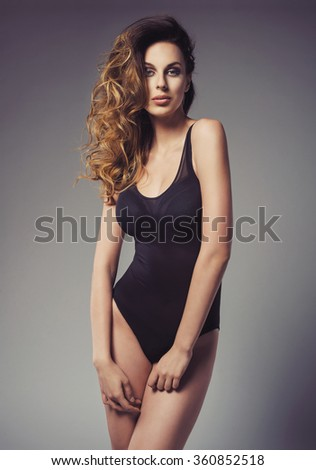 sexy fashionable young woman posing in a black swimsuit. Wonderful ombre hair