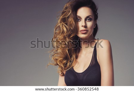 sexy fashionable young woman posing in a black swimsuit. Wonderful ombre hair - stock photo