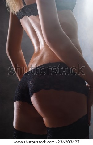 Sexy female back in lingerie on dark background