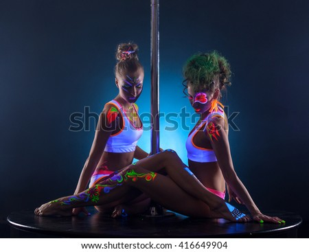 Sexy female dancers sitting together near pole - stock photo
