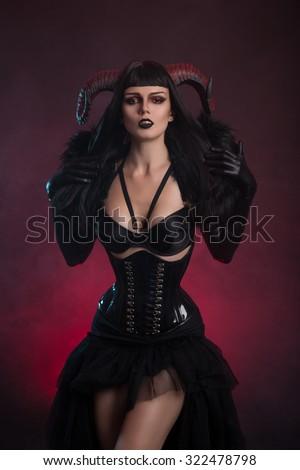 Sexy female demon in fetish costume, Halloween theme  - stock photo