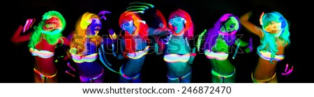 sexy female disco dancer poses in UV costume - stock photo