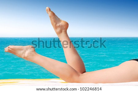 sexy female legs against turquoise sea - stock photo