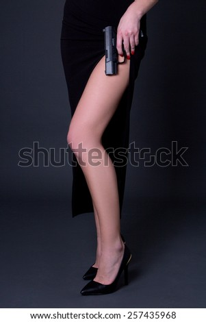 sexy female legs and gun over grey background - stock photo