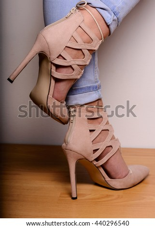 Sexy female legs in high-heeled suede shoes with lacing. - stock photo