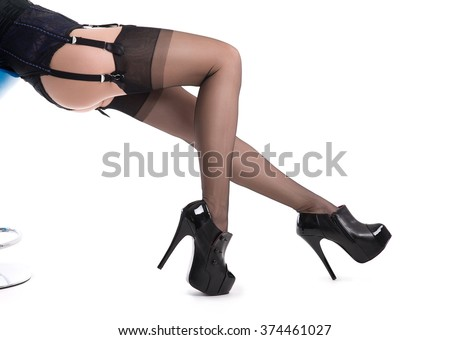 Sexy female legs in nylon stockings and high heel shoes, isolated on white background