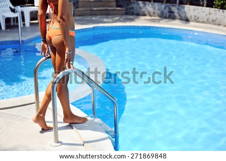 Sexy female legs near blue water of swimming pool - stock photo