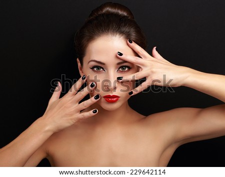 Sexy female model showing manicured hands near the makeup face on black background - stock photo