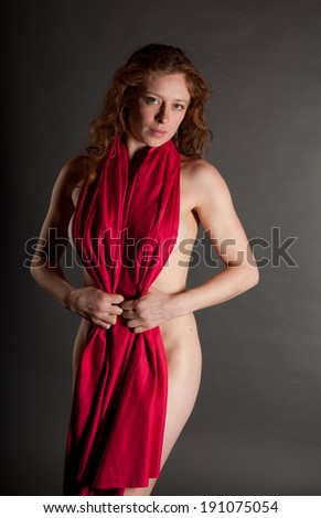 Sexy Female nude redhead with a red drape on a grey background