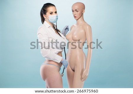 Sexy Female Nurse Wearing White Long Sleeves Shirt and Underwear with Mask, Gloves and Stethoscope Standing Besides a Human Dummy on a Very Light Blue Background. - stock photo