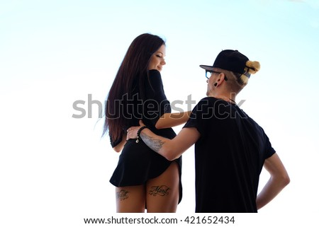 Sexy female posing with her boyfriend over blue sea. - stock photo