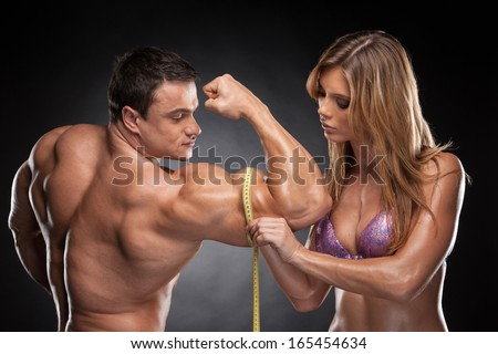 Sexy fit blond woman measure hand male  muscular. Standing together isolated over black background  - stock photo