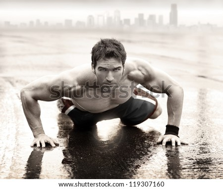 Sexy fit muscular man doing push-up on wet road with city skyline in the background