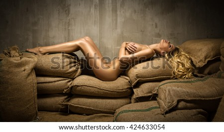 Sexy fit naked woman on sackcloth - stock photo