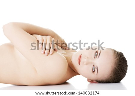 Sexy fit naked woman with healthy clean skin lying down, isolated on white