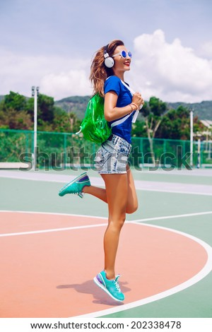Sexy fit sportive girl with perfect tan legs jumping at sports ground in bright casual outfit, with neon backpack sneakers and earphones, smiling dancing and having fun. - stock photo