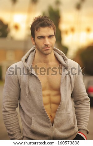 Sexy fit young man outdoors in golden light - stock photo