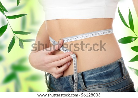 Sexy, fit, young woman measuring her waist - stock photo