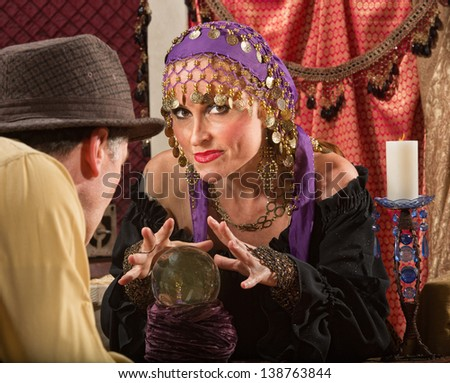 Sexy fortune teller waving hands over crystal ball - stock photo