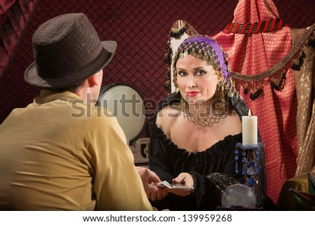 Sexy fortune teller with businessman and candle