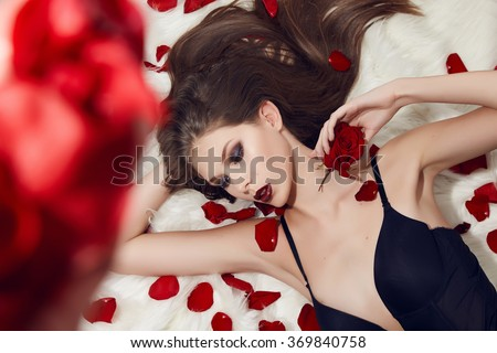 Sexy girl beautiful brunette in petals red roses in black silk underwear makeup beauty slim body porcelain skin is tender and sensual day of St. Valentine, the catalog lingerie, perfume and fragrance - stock photo