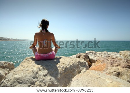 sexy girl doing yoga on the coast - stock photo