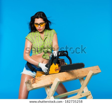 sexy girl holding a chainsaw - stock photo