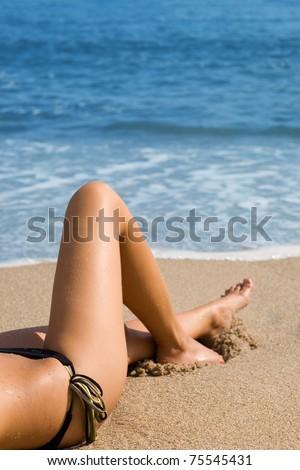 Sexy girl in a bikini lying on a beach. - stock photo