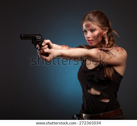 Sexy girl in a black dress holding a gun. Amazon girl. With blood on face. On dark background.  - stock photo