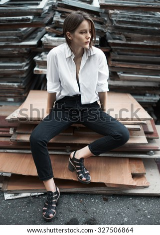 sexy girl in a white shirt in the slums outside the city on a sunny summer day - stock photo
