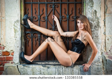 sexy girl in bikini posing fashion near red brick wall on the street.Shot of a sexy high fashion woman posing outdoor. Cute brunette with black bra posing on a city street - stock photo