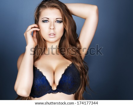 sexy girl in bra and long hair on dark blue background - stock photo