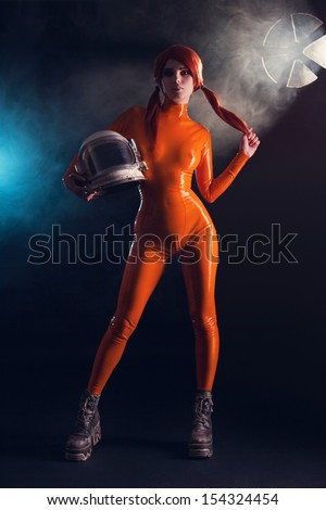 Sexy girl in orange latex catsuit holding helmet, sci-fi setting  - stock photo