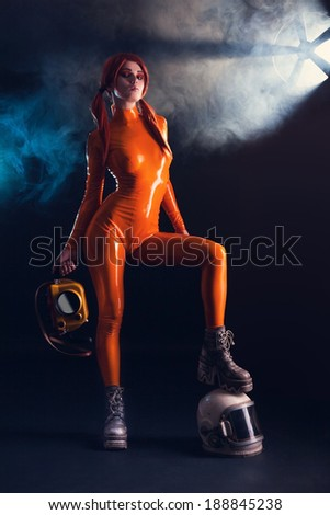 Sexy girl in orange latex catsuit with helmet and camera, sci-fi setting  - stock photo