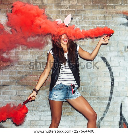 Sexy girl in rabbit ears waving red smoke bombs. Outdoors lifestyle portrait - stock photo