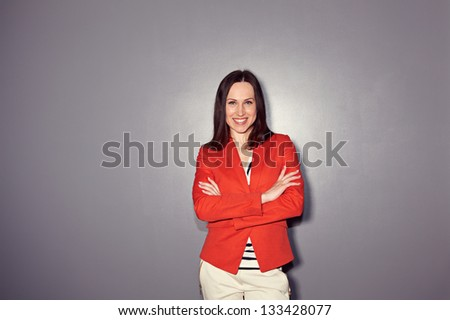 sexy girl in red coat looking at camera and smiling. studio shot over dark background
