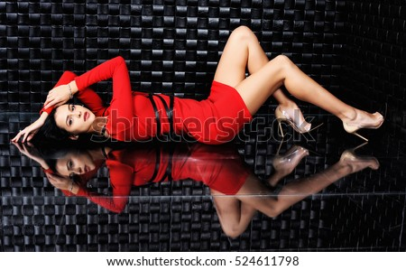 Sexy girl in red dress. Beautiful young woman lying on the mirrored floor.