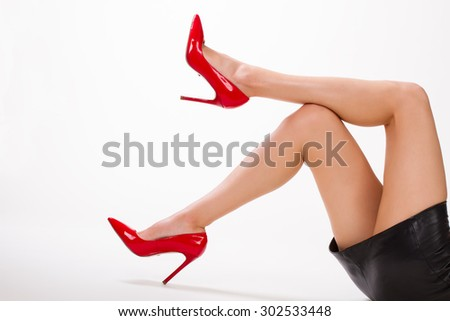 Sexy girl in red shoes and leather skirt. Girl moves her beautiful legs. - stock photo