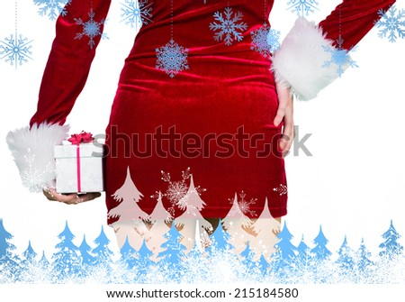 Sexy girl in santa outfit holding gift against snowflakes and fir trees