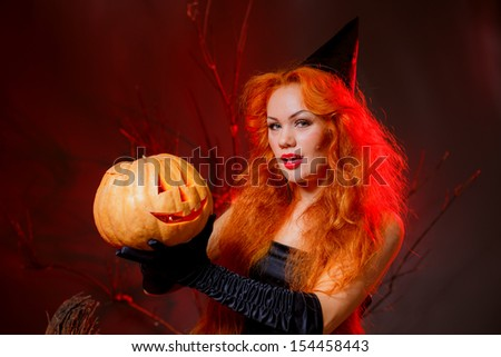 sexy girl in the image of a witch with a pumpkin on Halloween