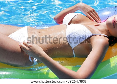 Sexy girl in white bathing suit. Wet body of young girl on mattress in the pool. Drops of water on beautiful body - stock photo