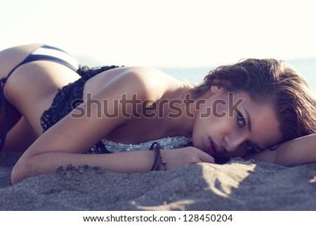 sexy girl lying at beach and looking at you. fashion portrait.