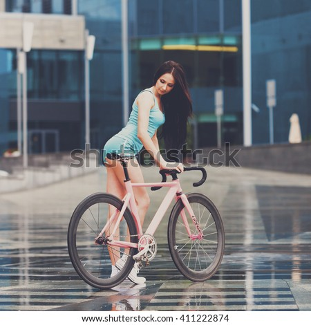 Sexy girl on bicycle. Young slim sexy sportive woman in blue shorts and white snickers long-haired, sensual posing on pink fix bicycle at grey background in urban city enviroment. Instagram style - stock photo