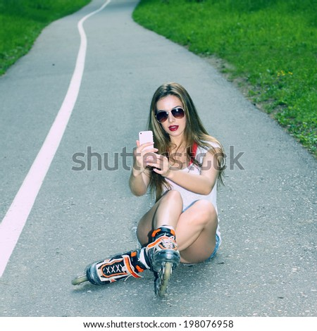 sexy girl on roller skates sitting on the road and photographed herself. Outdoor lifestyle. Nice girl doing Selfie.  - stock photo