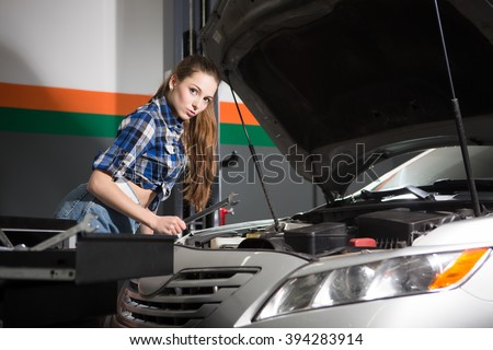 Sexy girl repairing automobile or car at repair shop. Long-haired lady is professional mechanic. Repairwoman looking at camera. - stock photo