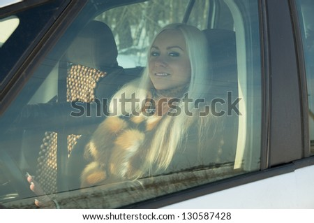 sexy girl sitting behind the wheel of a car winter