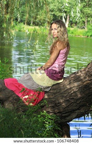 Sexy girl sitting on a tree by a river - stock photo